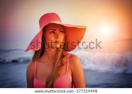 Beautiful girl in a hat on a background of sea sunset - stock photo