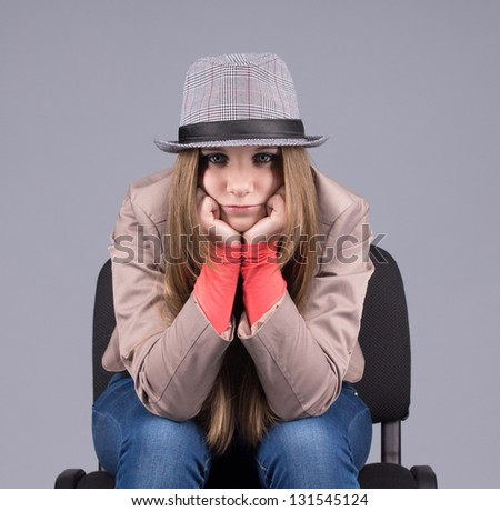 Beautiful girl in a hat on a chair sad - stock photo