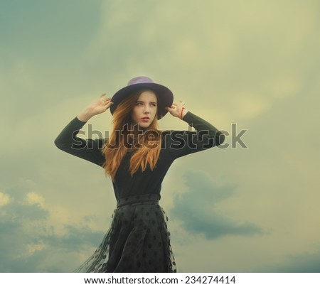 beautiful girl in a hat on a windy day - stock photo