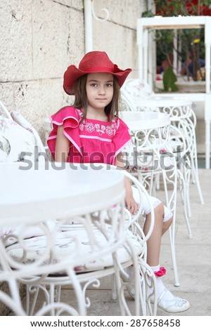 beautiful girl in a hat sitting on a white wrought furniture in the cafe - stock photo