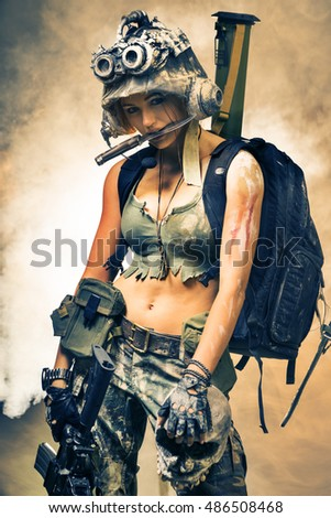 Beautiful girl in a helmet and with a gun in his hand