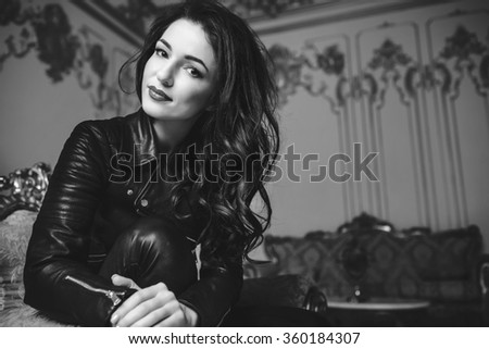 Beautiful girl in a leather jacket in a bedroom. Black and white