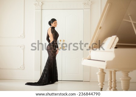 Beautiful girl in a long black dress standing at the piano.