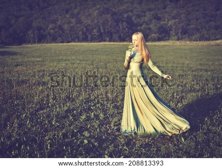 beautiful girl in a long green dress with a bouquet of flowers in the summer on the nature