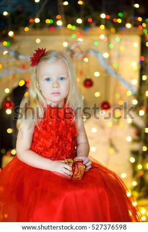 beautiful girl, in a long red dress, sits on a chair with a small gift in hands. On a background a set of bright festive sparks