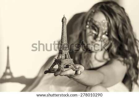 Beautiful girl in a mask holding Eiffel Tower - stock photo