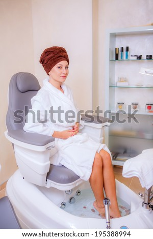 beautiful girl in a modern beauty salon, pedicure, salon, spa treatments a cosmetologist, nail care legs.   - stock photo