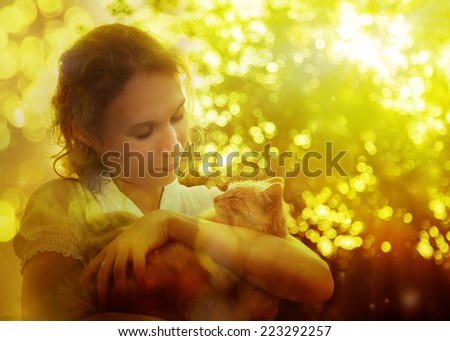 Beautiful girl in a park holding a kitten in her arms.