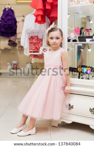 Beautiful girl in a pink dress in a store childrens clothes