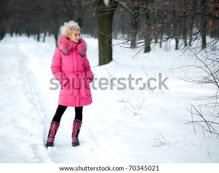 beautiful girl in a pink jacket in the winter against the backdrop of the park - stock photo