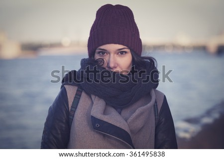 Beautiful girl in a red cap walks through the city of St. Petersburg. - stock photo