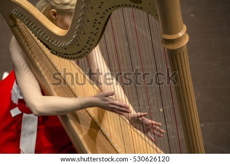 beautiful girl in a red dress playing the harp during concert at musical theater