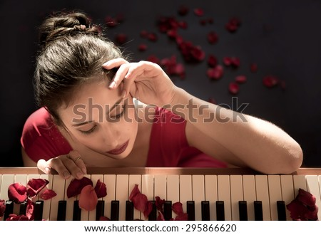 Beautiful girl in a red dress playing the piano - stock photo