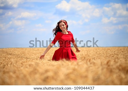 beautiful girl in a red dress walking through a wheat field.