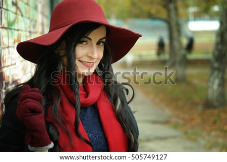 Beautiful girl in a red hat with a wide brim and a red scarf.