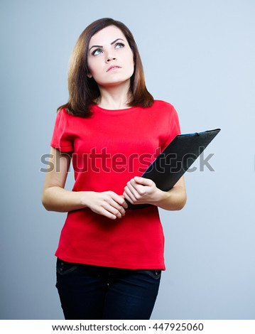 beautiful girl in a red T-shirt and jeans holding a folder and looking at the top, on a gray background