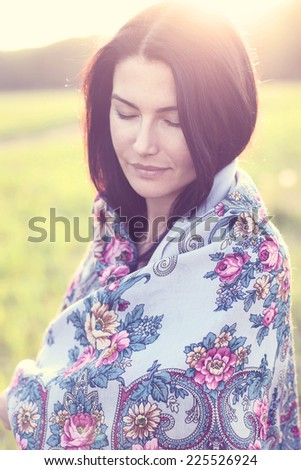 Beautiful girl in a scarf dreaming outdoors - stock photo