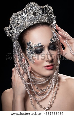 Beautiful girl in a silver crown and earrings on a dark background.