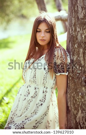 Beautiful girl in a summer dress leaning on an old tree
