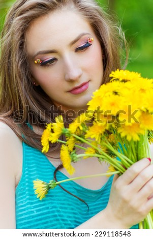 beautiful girl in a Sunny summer day walking in the garden and keeps yellow dandelions in the hands - stock photo