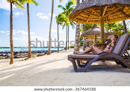 Beautiful girl in a swimming suit lying on a sun bed on the beach with a coconut in her hands looking into the beautiful island of Mauritius - stock photo