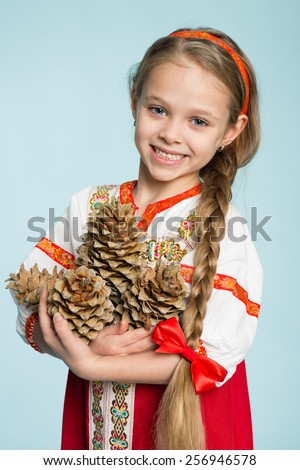 Beautiful girl in a traditional Russian folk costume holding pine cones. Girl seven years. - stock photo