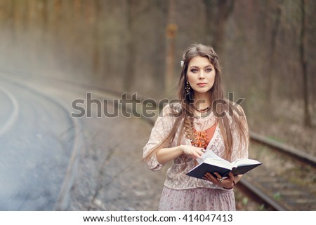 Beautiful girl in a vintage beige dress  standing between rails and reading the book in the park in early spring, reverie.
