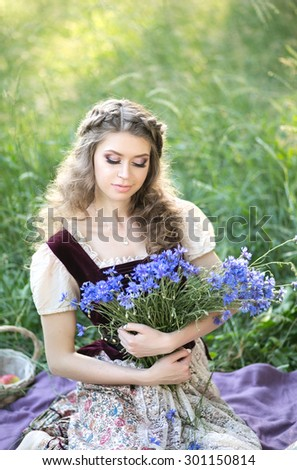 Beautiful girl in a vintage dress holding a rustic basket with bright blue cornflowers. summer, garden, village, sunset - stock photo