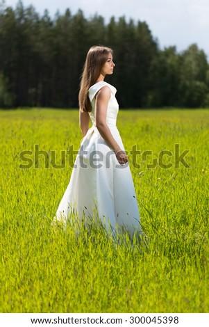 Beautiful girl in a wedding dress in the field - stock photo