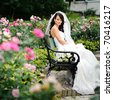 beautiful girl in a wedding dress sitting alone among the roses - stock photo
