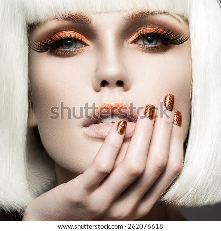 Beautiful girl in a white wig, with gold makeup and nails. Celebratory image. Beauty face. Picture taken in the studio. - stock photo