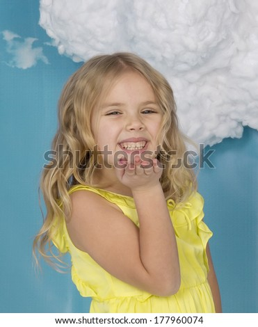 beautiful girl in a yellow dress laughs and sends an air kiss - stock photo