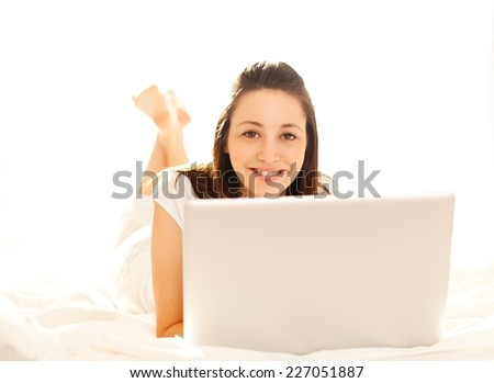 Beautiful girl in bed working on laptop - window in the background.