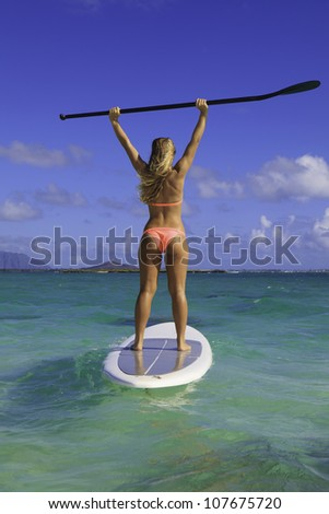 beautiful girl in bikini on her stand up paddle board