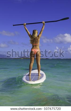 beautiful girl in bikini on her stand up paddle board - stock photo