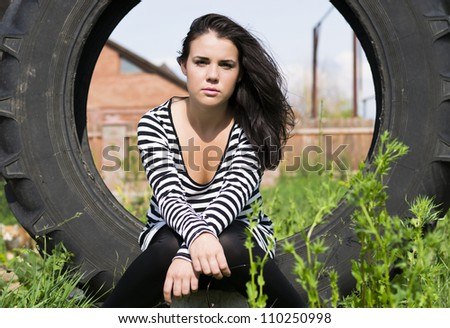 Beautiful girl in black dress inside the wheel of truck - stock photo