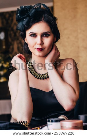 Beautiful girl in black dress posing . Party in style gangsters forties. - stock photo