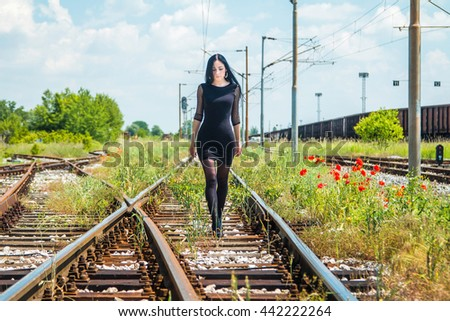 Beautiful girl in black dress walking on rail tracks - stock photo