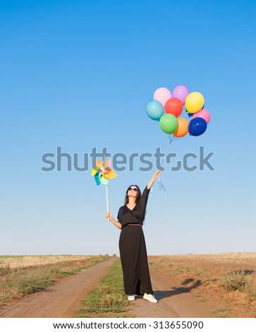 Beautiful girl in black dress with multicolored balloons and wind toy on countryside
