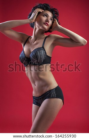beautiful girl in black lace lingerie sexy posing on a red background - stock photo