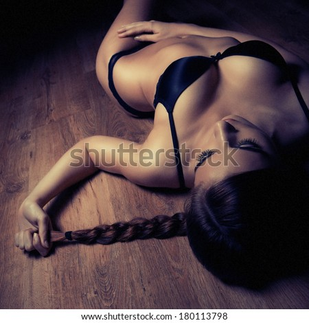 beautiful girl in black lingerie on timber floor - stock photo