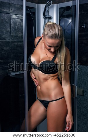 Beautiful girl in black lingerie with sexy body posing near the shower - stock photo