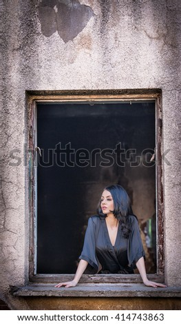 Beautiful girl in black posing in an old window frame. Attractive long hair brunette daydreaming in decaying building. Dark hair young woman with gorgeous eyes, photo concept in ruined house