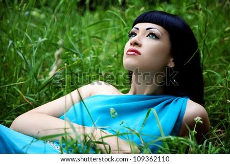 Beautiful girl in blue dress in grass - stock photo