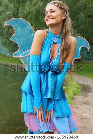 Beautiful girl in blue fairy costume with wings and a tiara in the park - stock photo