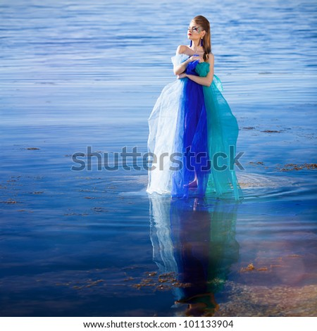 Beautiful girl in blue fantasy dress on the beach