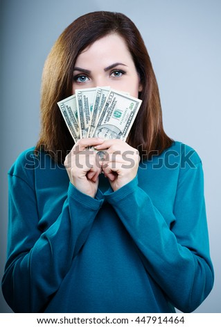 beautiful girl in blue shirt holding money near the face, on a gray background