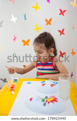 Beautiful girl in bright clothes sitting at the table and painting. Colorful false butterflies on background.