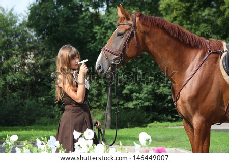 Beautiful girl in brown dress and chestnut horse portrait near the blooming flower bed