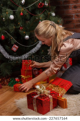 Beautiful girl in business attire sorting through the presents under the Christmas tree - stock photo